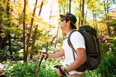 Young male hiker hiking in forest with walking poles, Arcadia, California, USA - stock photo