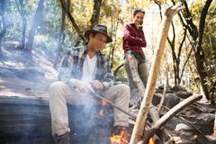 Young male and female hikers tending campfire in forest, Arcadia, California, - stock photo