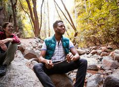 Young male and female hikers sitting on rocks in forest, Arcadia, California, - stock photo