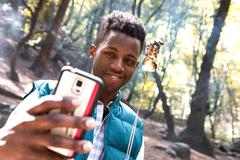 Young male hiker taking smartphone selfie with toasted marshmallow in forest, - stock photo