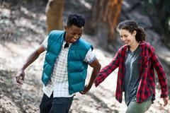 Young hiking couple holding hands whilst hiking in forest, Arcadia, California, - stock photo