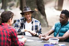 Three young adult hikers playing cards in forest, Arcadia, California, USA Stock Photos