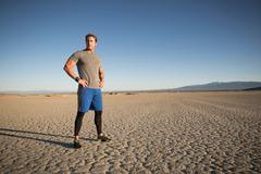 Man training, looking out from dry lake bed, El Mirage, California, USA - stock photo