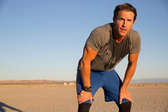 Man training, sweating and leaning forward on dry lake bed, El Mirage, - stock photo
