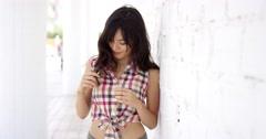 Beautiful woman wearing shirt tied at bottom - stock footage