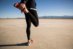 Waist down of man training, stretching legs on dry lake bed, El Mirage, Stock Photos