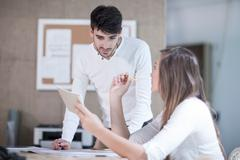 Young male and female designers having discussion in design studio Stock Photos