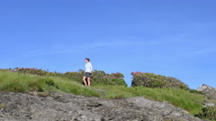 4K Slider Pan Woman Hikes Through Rhodo and Over Rocks Stock Footage