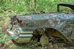 american Car abandoned in forest with gun bullet holes detail - stock photo