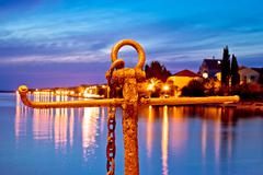 Rusty anchor view at blue evening - stock photo