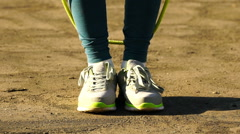 Woman jumping on a skipping rope in a park. HD video 120fps Stock Footage