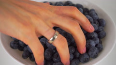 Female hand scooping blueberries from white plate 4K close up ProRes video Stock Footage