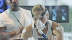 4K Female athlete training hard, being tested and monitored by sports scientist. Stock Footage