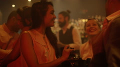 4K Bar staff serving drinks & chatting to customers in busy city bar. Stock Footage