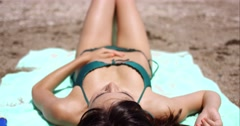 Woman suntanning on a tropical beach in summer sun - stock footage