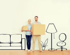 couple with cardboard boxes moving to new home - stock photo