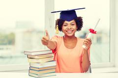 happy african bachelor girl with books and diploma - stock photo