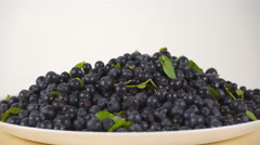 Girl scooping wet huckleberries from rotating plate 4K close up ProRes video Stock Footage