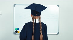 Portrait student 7-8 years graduate in the mantle turns at camera holding book Stock Footage