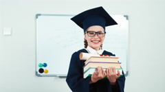 Student 7-8 years graduate in the mantle holding books and diploma turns at - stock footage