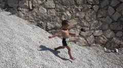 Slow motion small kid runs down a pile of pebbles.MP4 - stock footage