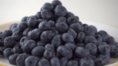 Heap of wet blueberries on a rotating plate 4K close up ProRes video - stock footage