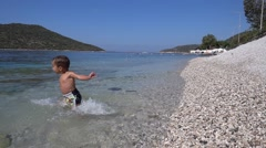 Slow motion small kid runs into the water.mp4 Stock Footage
