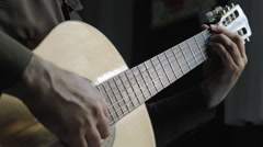 Man masterfully plays on classical acoustic guitar in the dark room close-up - stock footage