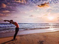 Young sporty fit woman doing yoga Sun salutation Surya Namaskar Stock Photos
