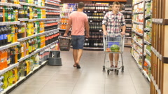 Young man with shopping cart buying juice at the supermarket - stock footage