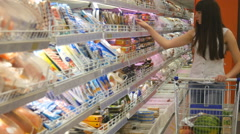 Young woman with shopping cart buying dairy or refrigerated groceries - stock footage