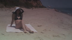 Girl brunette in black bathing suit and hat sunbathing on the beach by the sea Stock Footage