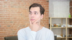 Waiting for inspiration. Thoughtful young man holding hand on chin ,looking away Stock Footage