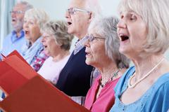 Group Of Seniors Singing In Choir Together Stock Photos
