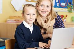 Teacher Helping Female Elementary School Pupil In Computer Class - stock photo