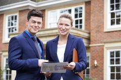 Male And Female Realtor Standing Outside Residential Property Stock Photos