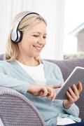 Mature Woman Streams Music From Digital Tablet To Wireless Headphones Stock Photos
