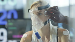 4K Female athlete on exercise bike being tested & monitored by sports scientist Stock Footage