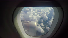 Cool view out airplane window of engine and clouds below - stock footage