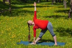Pregnant woman doing asana Utthita trikonasana outdoors Stock Photos