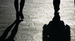 Shadows of four walking pedestrians projected on the sidewalk, accelerated Stock Footage