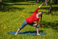 Pregnant woman doing asana Utthita parsvakonasana outdoors Stock Photos