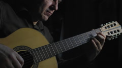 Man masterfully plays on classical acoustic guitar in the dark room Stock Footage