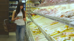 Girl coming up to the fridge, taking product and putting it into the basket Stock Footage