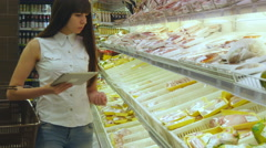 Woman buying refrigerated groceries at supermarket and using tablet pc - stock footage