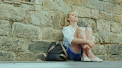 Tired woman sitting in an old building wall. Concept - get lost in an unfamiliar Stock Footage