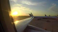 Out plane window - sun with plane in flight and one backing away from gate Stock Footage