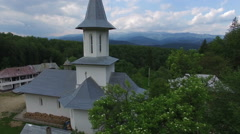 Christian church surrounded by green forest, mountain range, aerial view Stock Footage