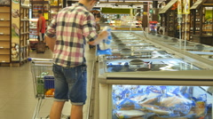 Guy coming up to the fridge in shop and taking product from it. Rear view Stock Footage