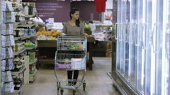 4K Customers shopping in supermarket, focus on woman with shopping cart Stock Footage